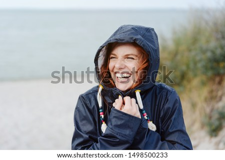 Laughing happy young woman embracing the cold autumn weather snuggling into her warm anorak with a beaming vivacious smile as she strolls along a beach #1498500233