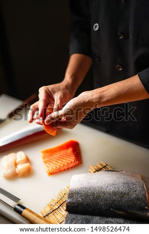Closeup of chef hands preparing japanese food. Japanese chef making sushi at restaurant. Young chef serving traditional japanese sushi served on a cuting board in lighting studio .  #1498526474