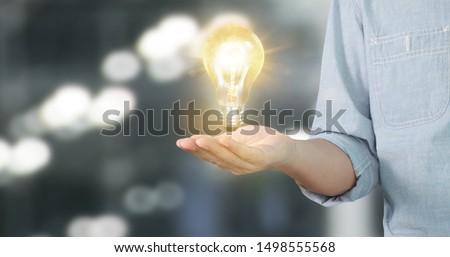 Hand of holding illuminated light bulb, idea, innovation inspiration concept #1498555568