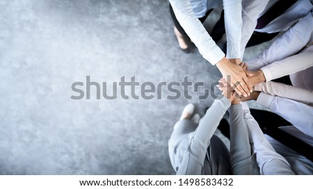 Close up top view of young business people putting their hands together. Stack of hands. Unity and teamwork concept. #1498583432