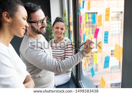 Business people meeting at office and use post it notes to share idea. Brainstorming concept. Sticky note on glass wall. #1498583438