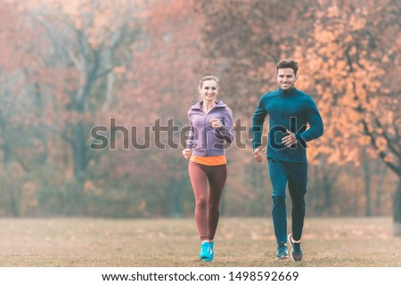 Couple in wonderful fall landscape running for better fitness towards the camera #1498592669