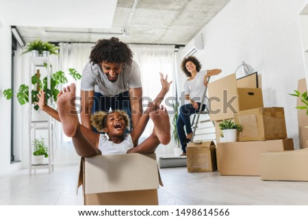 Happy playful  African American family moving in new apartment, little preschooler daughter sitting in cardboard boxes, father rolling her,  purchase property concept Royalty-Free Stock Photo #1498614566