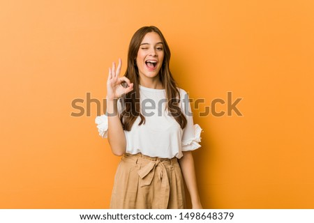 Young caucasian woman winks an eye and holds an okay gesture with hand. #1498648379