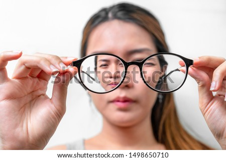 Asian woman holding glasses on white background, Selective focus on glasses , myopia and eyesight problem concept. Royalty-Free Stock Photo #1498650710