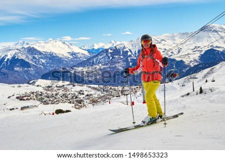 Les Sybelles, France - March 12, 2019: Woman skier posing on the ski slopes above La Toussuire village in France, Les Sybelles ski domain, on a perfect sunny day with blue sky. #1498653323