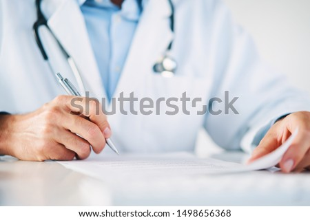 Close up of doctor reading and signing files and paperwork of patient #1498656368