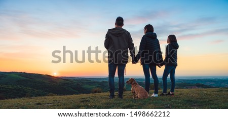 Family with dog embracing while standing on the hill and looking at sunset