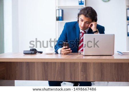 Young male businessman working in the office #1498667486