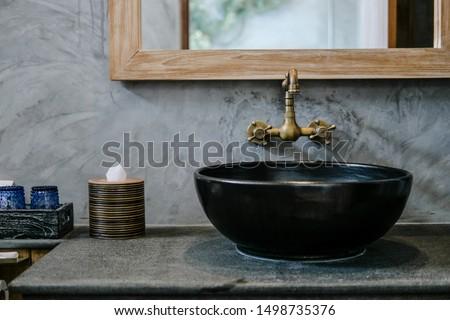Black sink, vintage copper faucet, gray wall, mirror, loft bathroom interior details. Close up, minimalism concept #1498735376