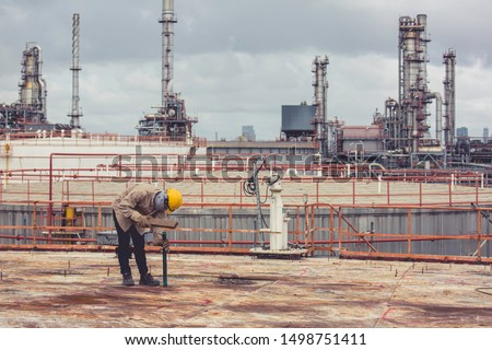 Male  worker wearing protective clothing cleaning roof oil storage tank industrial construction #1498751411
