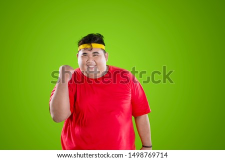 Successful loss weight concept. Young fat man wearing sportswear while expressing happy in the studio #1498769714