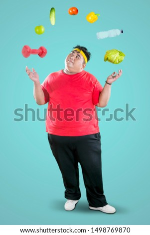 Picture of overweight man wearing sportswear while juggling dumbbell and foodstuff in the studio