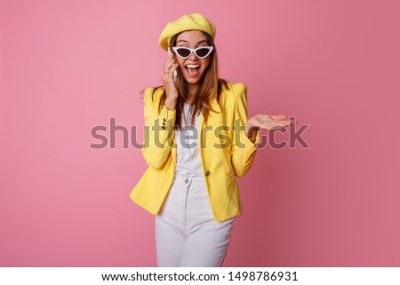 Stylish business woman talking by mobile phone with surprise emotions. Wearing yellow jacket and beret, standing over pink background. #1498786931
