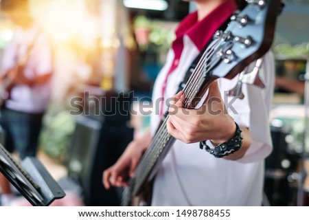 A girl student playing a bass in group on the stage. This photo selective focus. #1498788455