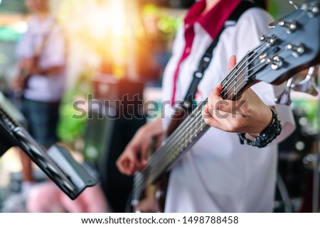 A girl student playing a bass in group on the stage. This photo selective focus. #1498788458