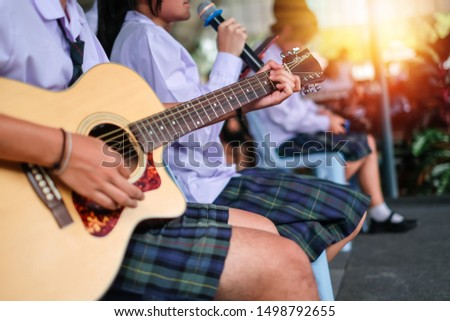 a boy student playing a guitar in string group on the stage. this photo selective focus. #1498792655