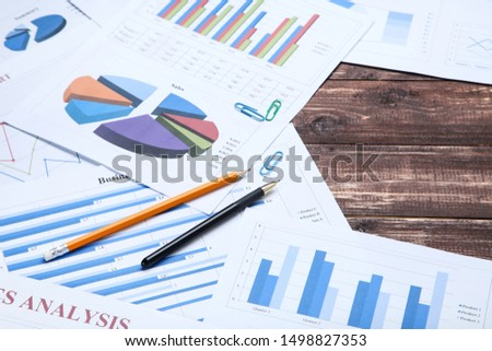 Financial papers with graph and charts on wooden table #1498827353