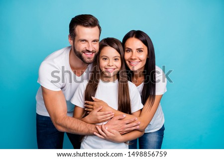 Portrait of lovely adult guy woman and cute kid hug piggyback wearing white t-shirt denim jeans isolated over blue background