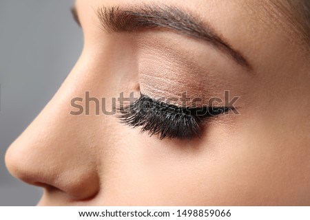 Young woman with elegant makeup and long eyelashes on grey background. Eyelash extensions #1498859066
