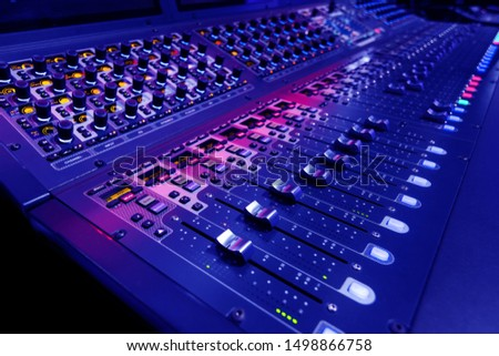 Professional audio studio sound mixer console board panel with recording , faders and adjusting knobs,TV equipment. Blue tone and close-up image. #1498866758
