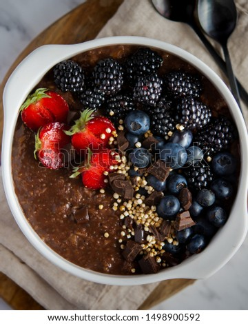 Intensively chocolate oatmeal topped with season fruits: strawberries, blueberries and blackberries, small pieces of chocolate and quinoa. Served in a round white bowl on a wooden board. Top view. #1498900592