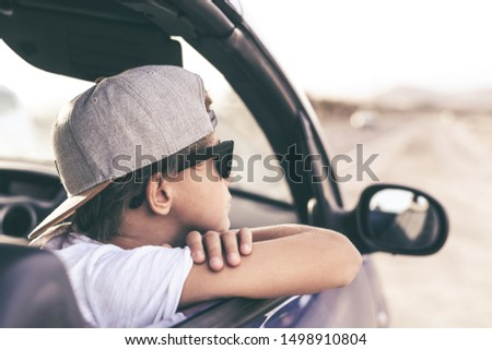 Thoughtful trendy boy enjoying summer day sitting in the car. Portrait of a caucasian teen looking out of the car window. Cool teenager with rapper hat, looking away. Youth, carefree, freedom concept. #1498910804