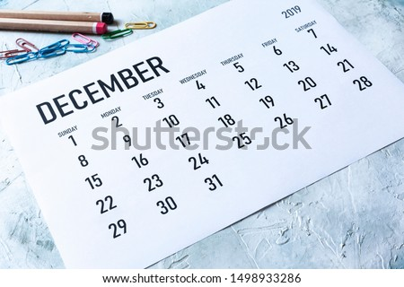 Simple 2019 December monthly calendar on table with office supplies #1498933286