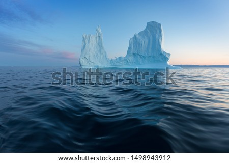 Icebergs in front of the fishing town Ilulissat in Greenland. Nature and landscapes of Greenland. Travel on the vessel among ices. Phenomenon of global warming. Ices of unusual forms and colors.