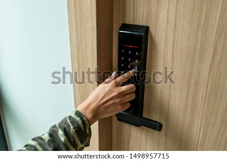 Closeup of a woman's finger entering password code on the smart digital touch screen keypad entry door lock in front of the room. Self Check-in, Modern security,Temporary codes.  Royalty-Free Stock Photo #1498957715