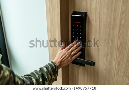 Closeup of a woman's finger entering password code on the smart digital touch screen keypad entry door lock in front of the room. Self Check-in, Modern security,Temporary codes.  #1498957718