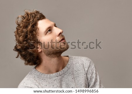 Profile portrait of gorgeous cute handsome young man with perfect features, bristle and reddish hair posing at blank copyspace wall in jumper, looking up with inspired dreamy facial expression #1498996856