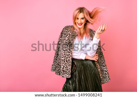 Young pretty sexy magnificent woman playing with her hairs, wearing evening sparkling cocktail outfit and fur leopard printed trendy coat, pink background, positive emotions. #1499008241