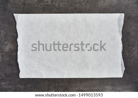 Crumpled piece of white parchment or baking paper on black concrete background. Top view. Copy space for text and design element. #1499013593