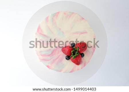 Birthday cake with strawberries, blueberries and blackberry on white background. Picture for a menu or a confectionery catalog. Top view.