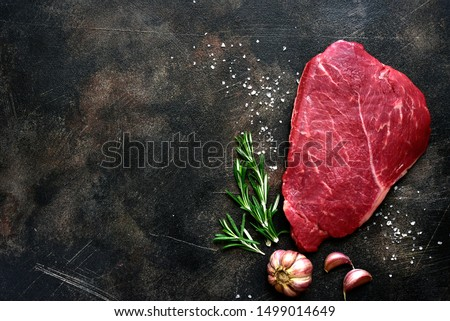 Raw beef steak with spices on a dark slate, stone or concrete background. Top view with copy space. #1499014649