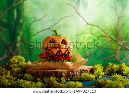 Halloween party burger in shape of scary pumpkin  on natural wooden board. Halloween food concept. #1499027513