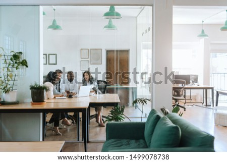 Diverse group of businesspeople sitting together around a table inside of a glass office boardroom and working on a laptop #1499078738