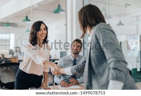 Smiling young businesswoman shaking hands with a coworker during a meeting with colleagues around a table in an office boardroom #1499078753