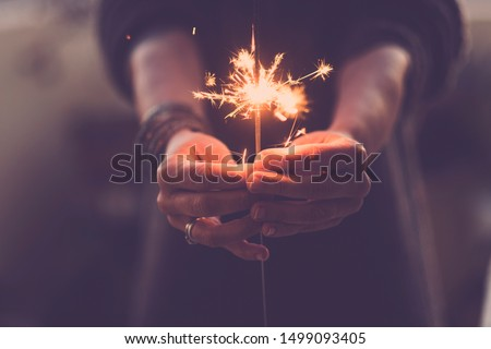 Concept of party nightlife and new year eve 2020 - close up of people hands with red fire sparklers to celebrate the night and the new start - warm colors filter #1499093405