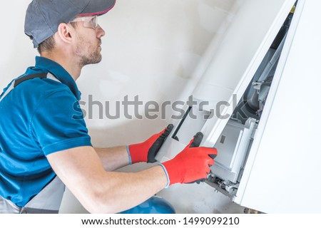 House Heating Unit Repair by Professional Technician. Closeup Photo. Home Equipment Issues.   Royalty-Free Stock Photo #1499099210