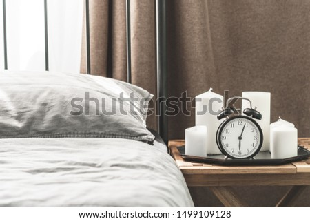 Cozy gray bedroom interior with comfortable bed near the wooden night table with candle, alarm clock and dried flowers. Cozy atmosphere at home. Warming up the cold winter or autumn evenings. #1499109128