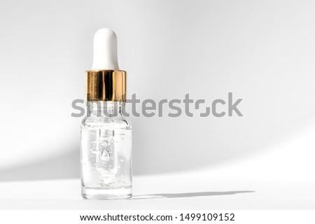 Anti aging serum in glass bottle with dropper on white background. Facial liquid serum with collagen and peptides. Skincare essence for beautiful healthy skin. #1499109152