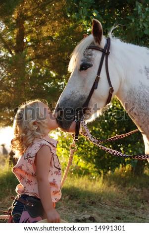 Little girl kissing pony.
