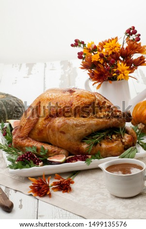 Garnished traditional roasted turkey for Thanksgiving, garnished with fresh figs, pomegranate, and herbs. Pumpkins, fall flowers, and decorations. #1499135576