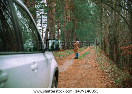 car travel concept woman got out from white suv car at forest trail to take picture on phone autumn season