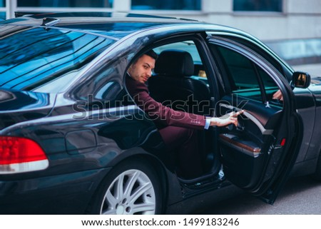 Handsome suited businessman entering the back of his black limo. #1499183246