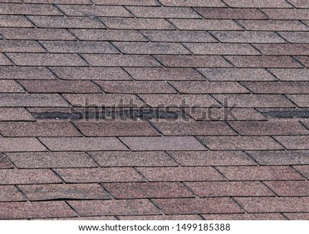 Composite shingles damaged on roof by storm with strong winds. #1499185388