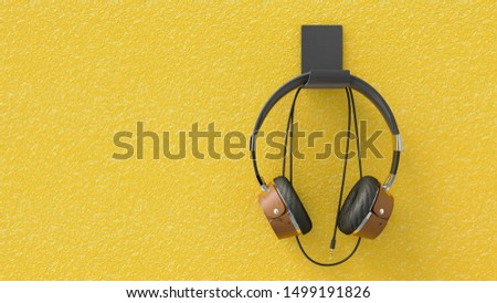 Vintage headphones hanging on the yellow wall with clipping path. 3D Render.