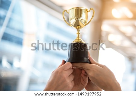 Champion golden trophy for winner with sport player hands in sport stadium background. Success and achievement concept. Sport and cup award theme. American football award and match game play prize #1499197952